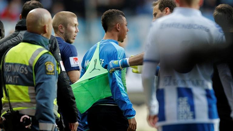 Malmö FF:s Tobias Sana leds bort från IFK-klacken efter att han träffats av en smällare (och reagerat med att kasta upp en hörnflagga) under onsdagens allsvenska fotbollsmatch mellan IFK Göteborg och Malmö FF på Gamla Ullevi i Göteborg.