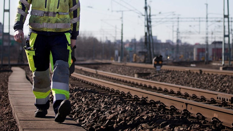 En man går vid tågspåret.