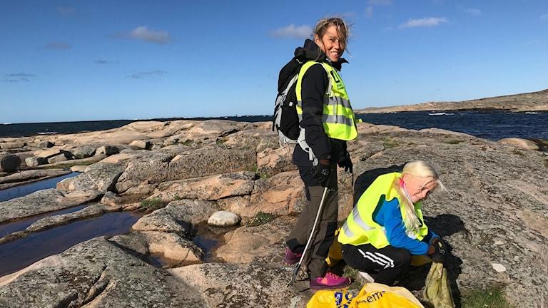 Mia Elofsson och dottern Stina Elofsson står på en klippa i Sotenäs. De har på sig gula reflexvästar och säckar att plocka skräp i. Det är lite moln på himlen och vågor på vattnet men solen skiner.