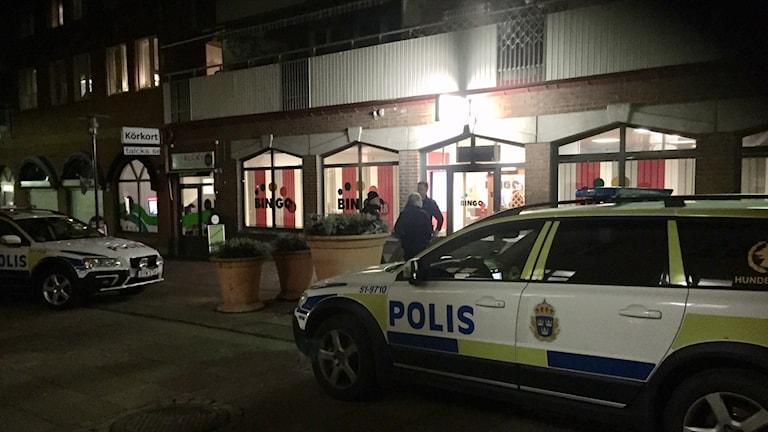 Flera polisbilar och poliser utanför bingolokalen. det är mörkt.