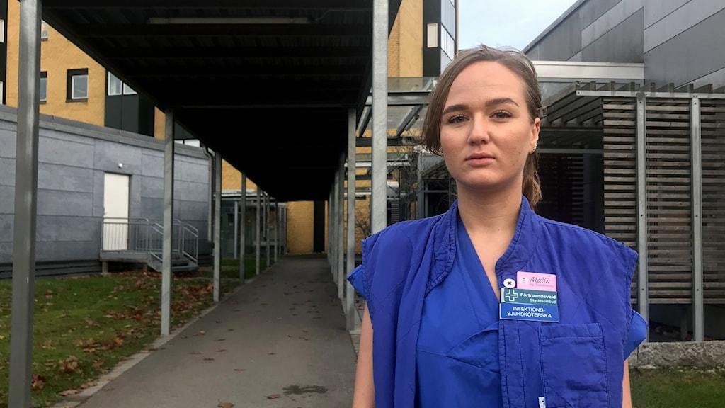 Malin Cardesjö, sjuksköterska, står i sina blåa arbetskläder framför infektionsavdelningen på NÄL i Trollhättan.