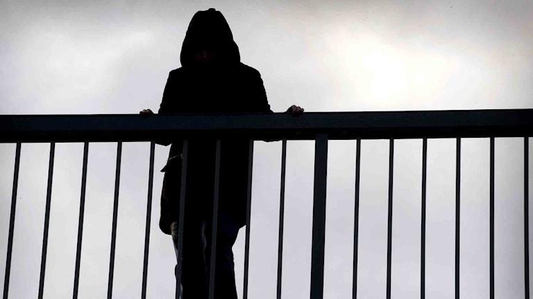 Siluett av en kvinna på bro