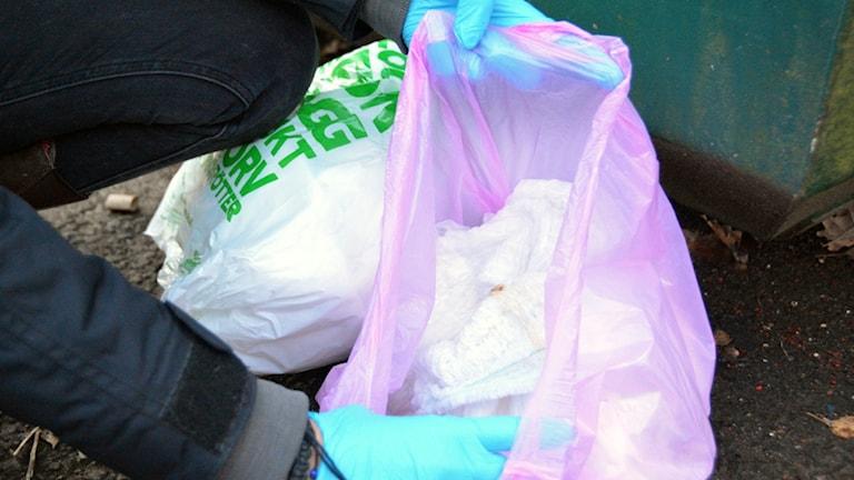 Bild på blöjor i plastpåsar vid contaioner.
