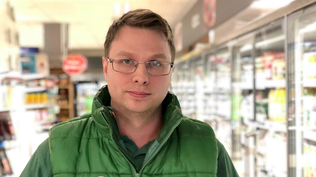 Joachim Gylebrandt, ung kille med glasögon. Han är brunhårig, ler lite busigt. Har en grön Coop-väst på sig, och grön skjorta.