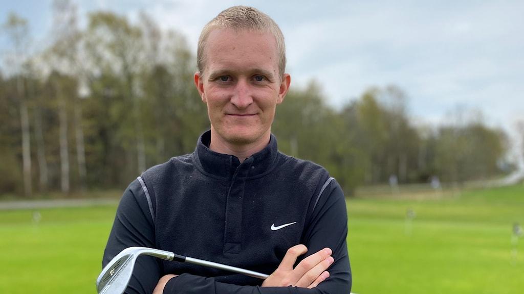 Golfspelaren Marcus Kinhult står med armarna i kors och håller i en golfklubba på golfbanan med träd i bakgrunden