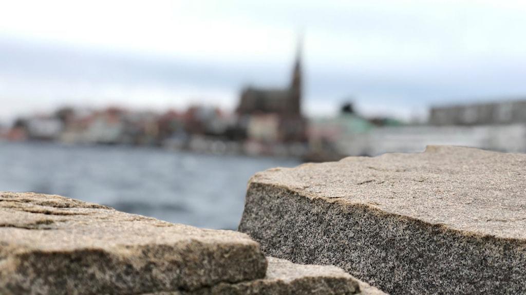 Lysekils stadssilhuett, den är suddig. I förgrunden syns stenar, klara.