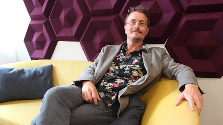 Stefan Björling sitter i en gul soffa