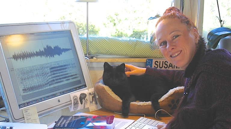 Forskaren Susanne Schötz sitter framför sin dator med en katt.