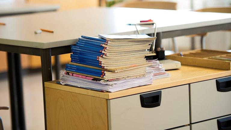 Genrebild av en hög skolböcker som ligger ovanpå en hurts i ett klassrum. I bakgrunden syns skolbänkar och pennor.