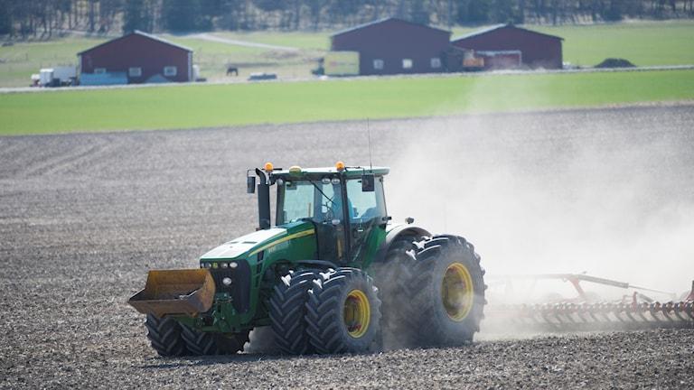 Bild på en traktor på en åker.
