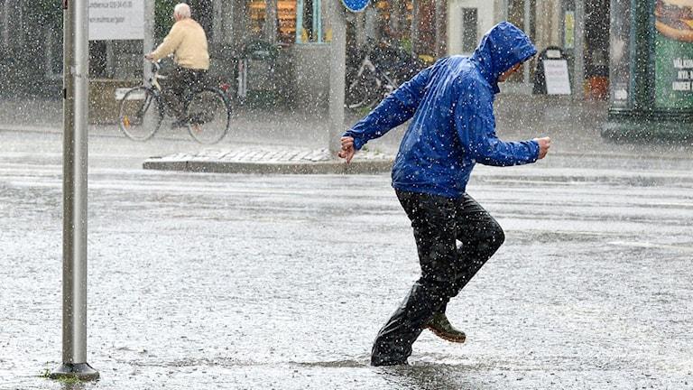 Bild på en man som vadar i högt vatten en sommardag.