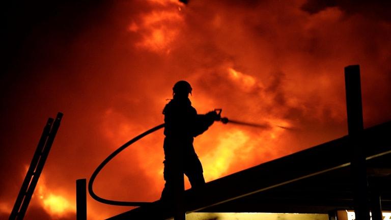 Silhuett av en brandman som släcker en brand.