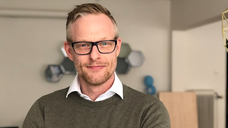 Peter Eriksson bär en militärgrön flis-tröja med vit skjorta innaför. Han har svarta glasögon, med modern ram. Lite gråhårig vid sidorna, blond på toppen. Han ler lurigt. Har snälla, blida ögon. Och lite skäggväxt.