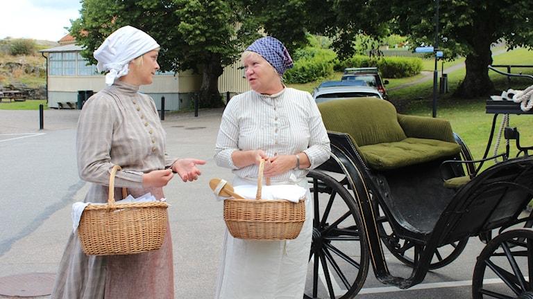 Två kvinnor i kläder från sent 1800-tal står och pratar framför en häst och vagn.
