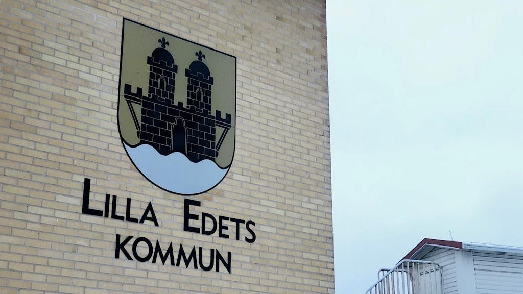 Lilla Edets kommunlogga avtecknad på kommunhuset i staden. En byggnad av beige tegel; rätt härlig ton.