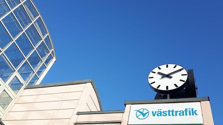 Västtrafik i Uddevalla snett underifrån bild på klocka och Västtrafik-skylt