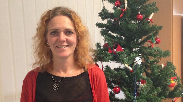 Anette Alexandersson framför en gran. Foto: Charlott Holmåker/Sveriges Radio.