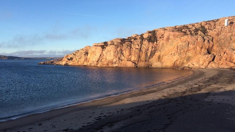 En strand, havet och ett berg.