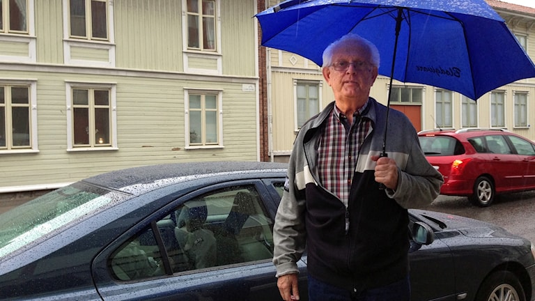 Gunnar Ahnblom står framför sin bil med ett blått paraply