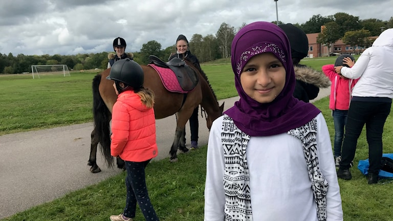 Kawsar Ali, 10 år, står framför ponnyhästar som är på besök på Restad gård