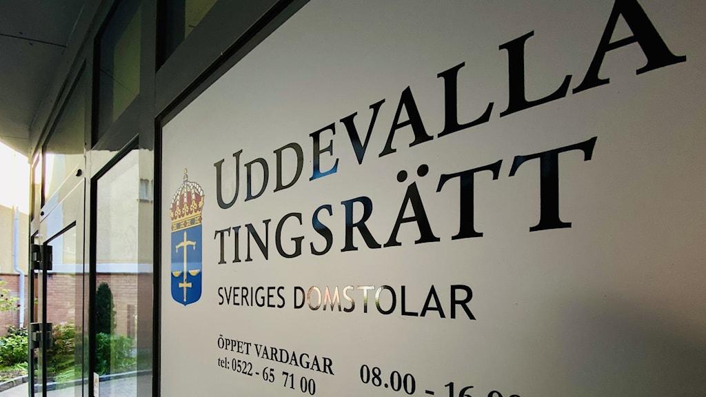 En bild på en skylt som står utanför tingsrätten i Uddevalla. Skylten förkunnar att här ligger Uddevalla tingsrätt, en del av svenska rättsväsendet.