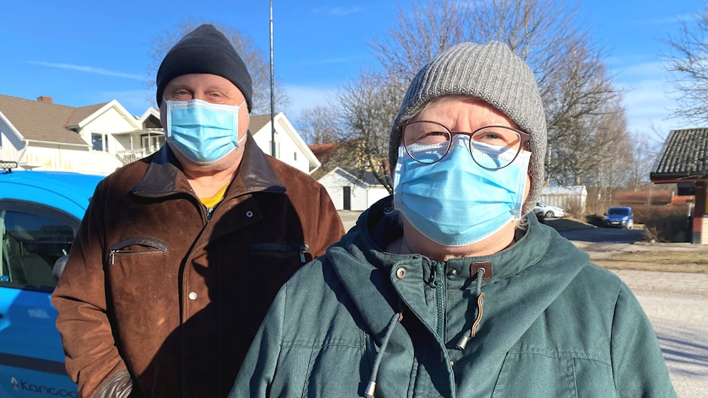 Porträttbild utomhus på syskonparet Mona-Lisa Hansson och Bo-Anders Hansson. Båda har blå munskydd på sig, mössor och jackor.