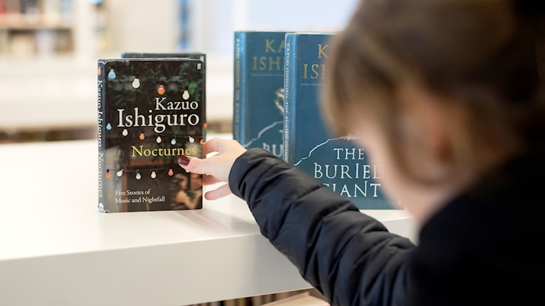 En kvinna sträcker sig efter en uppställd bok på en hylla.
