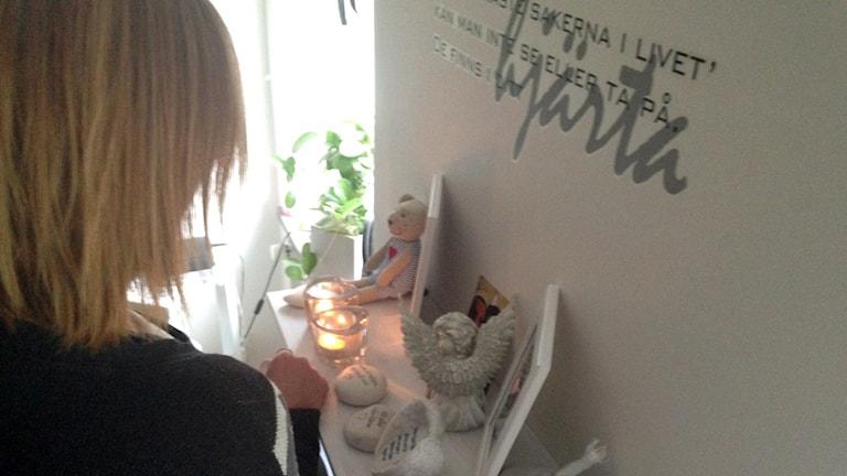 Bild bakifrån på kvinna som står vid en minneshylla med änglar och tända ljus.