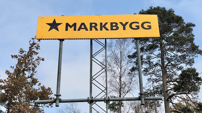 En skylt med Markbygg-loggan. Den består av texten MARKBYGG men också en svart stjärna, tecknat på en gul bakgrund.