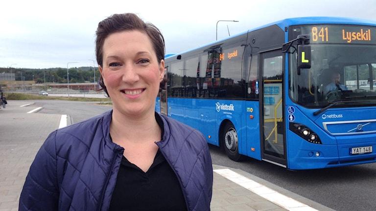 Porträttbild av Kajsa Sandblom framför en blå buss. Foto: Carin Österdal Sveriges Radio P4 Väst