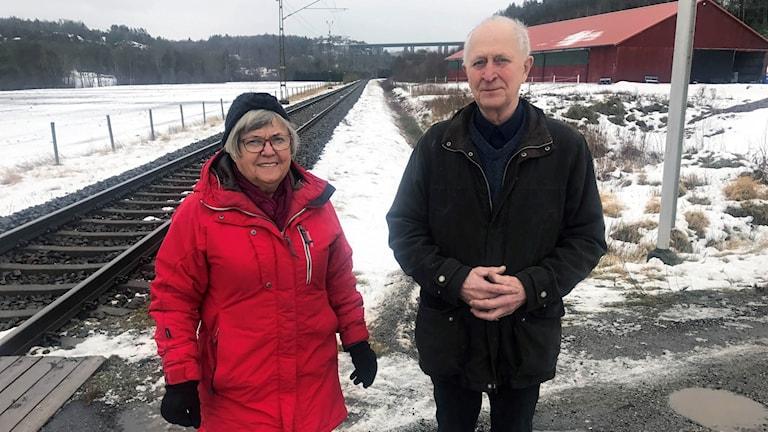 Anita och Sture framför järnvägsövergången i Berg i Ödsmål. Lite längre bort till vänster hamnade deras bil efter krocken med tåget.