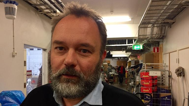 Bild på ica-chefen Fredrik Nyqvist. Han står i lagret, i bakgrunden syns ett kaos av paket och annat lagermaterial. Fredrik e skäggig och lite gråhårig.