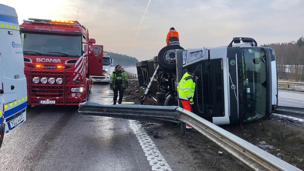 En lastbil som ligger på sidan på E6-an. Räddningsfordon på plats.