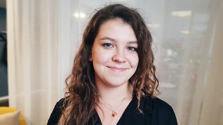 Porträtt av violinisten Lisa Chenevier. Hon har ljusbrunt lockigt hår och ler in i kameran.