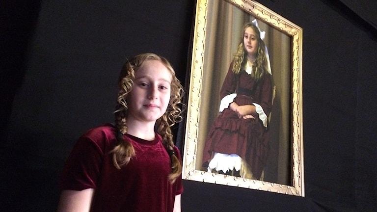 Flicka framför tavla av Kulla-Gulla