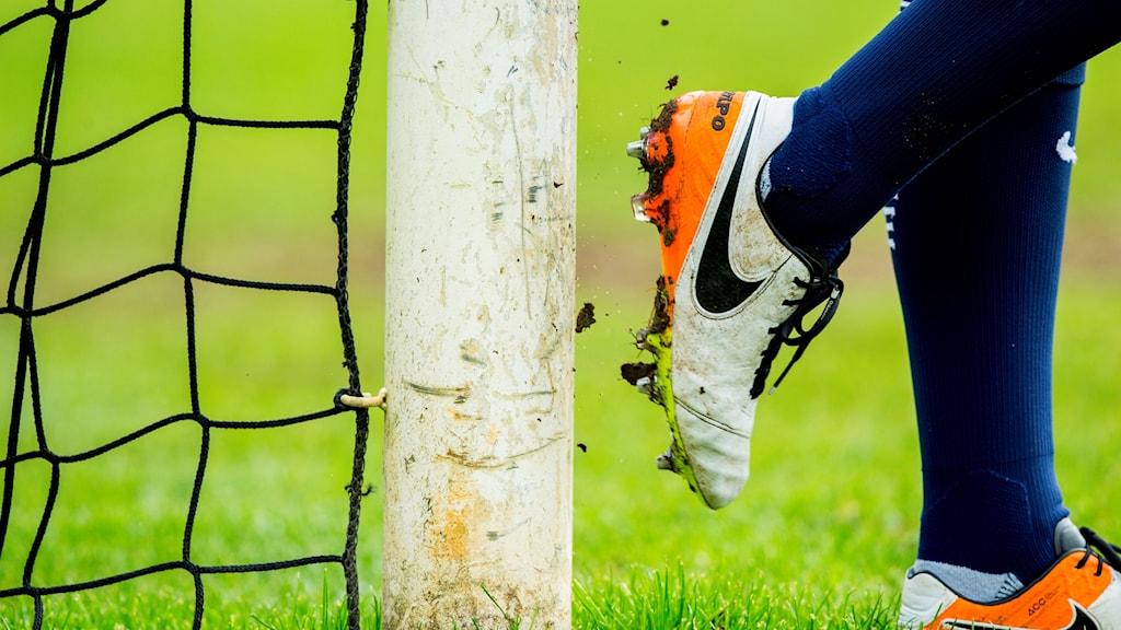Bild på en fotbollsspelares skor vid ett fotbollsmål.