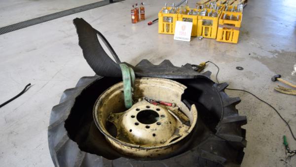Ett uppbrutet traktorsdäck där spritflaskor har förvarats