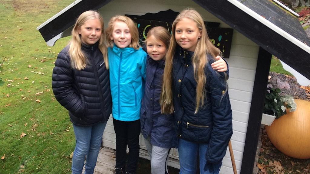 fyra flickor framför en lekstuga