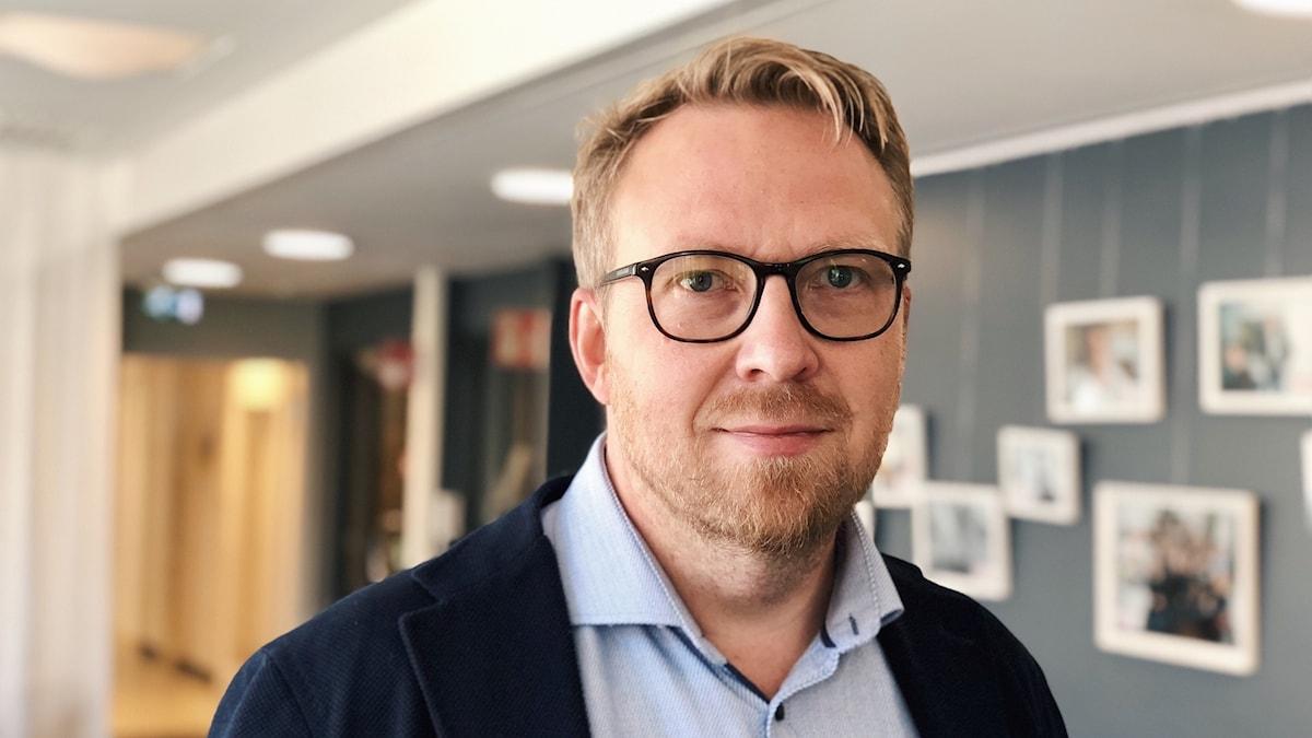 Porträtt av Henrik Sundström. Han har ljusblå skjorta, mörkblå kavaj, glasögon med svarta bågar och ljust hår och skägg.