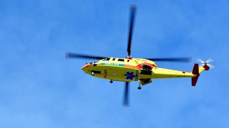 Ambulanshelikopter lyfter mot en blå himmel.