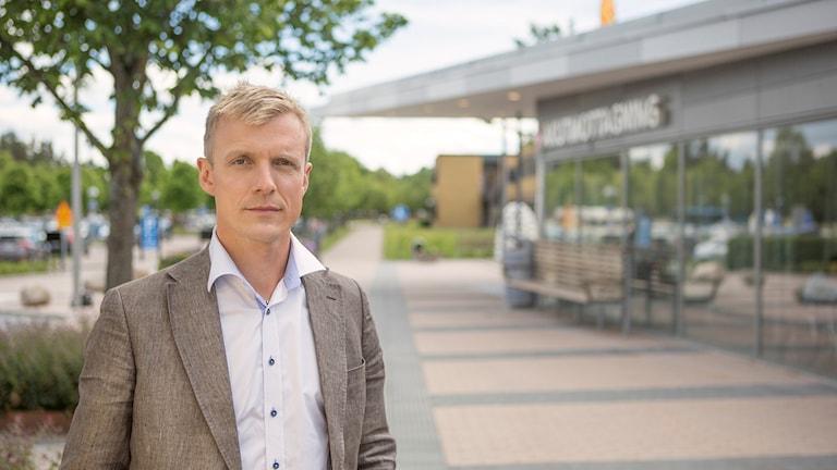 Porträtt av moderaten Martin Andreasson. Han står ute på gatan, det är sommar och han har ljusblå skjorta och grå kavaj.