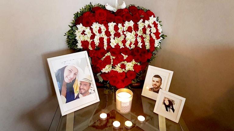 Ett hjärtformat blomsterarrangemang, flera foton och några levande ljus på ett bord.