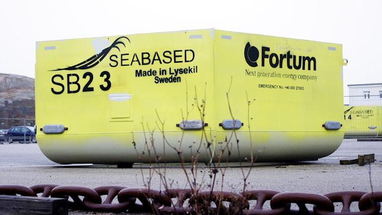 """På bilden ses en stor gulmålad boj tillverkad av vågkraftsbolaget Seabased. Den är fotograferad från sidan så det syns inte om den är fem- eller sexkantig. Offeranoder i form av rejäla zinktackor är fästade på bojen, två på varje sida. På den nästan lysande gulmålade bojen ses två loggor, dels Seabaseds, dels Fortums. Under Seabaseds logga står """"Made in Lysekil Sweden"""" och bredvid en individmärkning för bojen: SB23."""