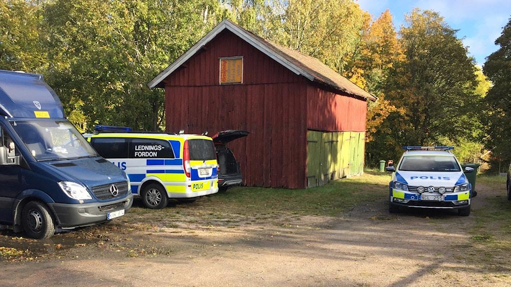 Fordon och polisbilar vid ett rött hus och en grusväg.