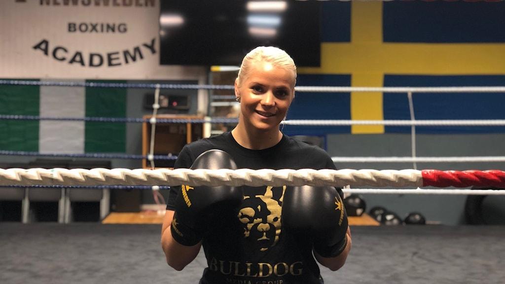 Marianne Ahlborg står i boxningsringen och ler in mot kameran.
