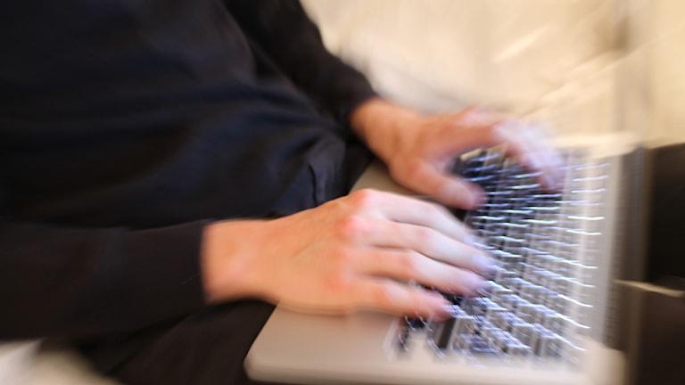 Inzoomat tangentbord med fingrar som skriver på det