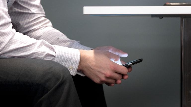 En person sitter och pillar på sin mobil under bordet
