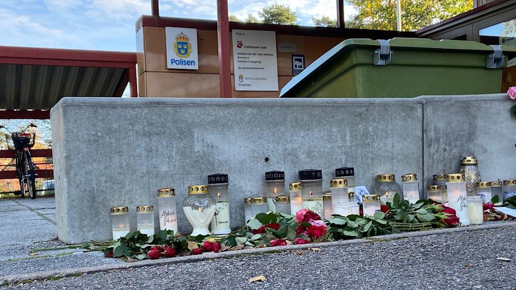 Tända begravningsljus och blommor utplacerade utanför polisens arrest.