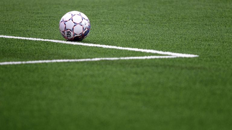 En vit fotboll ligger på en grön fotbollsplan.