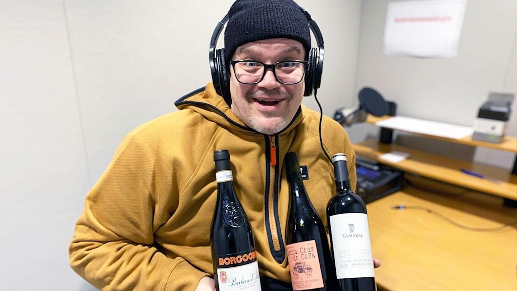 Dan Luthman iklädd mössa och gul hoodie ler in i kameran. I handen håller han tre flaskor rödvin.